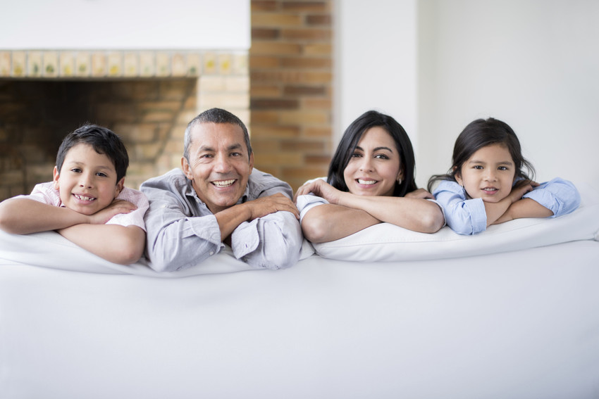 Latin family portrait looking very happy at home leaning on a sofa and looking at the camera