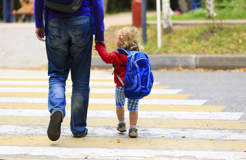 father walking little daughter with backpack to school or daycare
