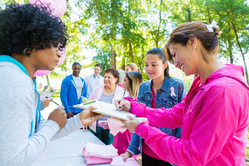 Diverse group of adults and teenagers are lined up at registration table in sunny park. They are signing up to run in charity 5k race or marathon to raise money for breast cancer research. People are wearing pink athletic clothing and breast cancer awareness ribbons.