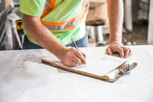 Construction worker making notes on a clipboard