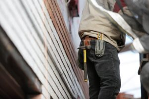 Man with a tool belt outside of a house